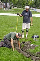Two retired adult men working in second career install lawn irrigation systems
