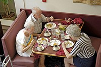 Senior trio eats dinner together in a social setting in a retriement home