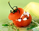 Stuffed tomato with mozzarella on rocket and potato sauce