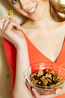 Young woman holding bowl of nuts and raisins