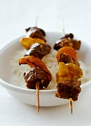 Two beef and vegetable kebabs on rice