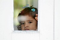 Four years old Indian baby girl through a window. India