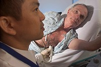 Close-up of a male sonographer performing an ultrasound cardiac examination on a male patient.