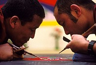 Buddhist monks working on a mandala sand painting. This is an artistic tradition of Tantric Buddhism in which colored sand is laid on a flat platform ...