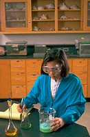 Young girl in chemistry classroom wearing safety goggles.