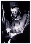 Surgeon during operation wearing a magnifying loupe with light.