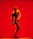 Male body builder posing against red background.