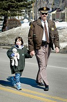 Policeman helps little girl to cross the road.