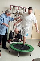 MAN IN PHYSICAL THERAPY<BR>Patient and health professional.<BR>Exercising on a trampoline to develop balance (proprioception ) before resuming athleti...
