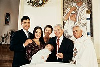 Portrait of a Family Standing by a Baptismal Font With Their Baby and a Priest