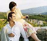 Young Couple Looking at View and Enjoying a Glass of Red Wine