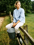 Famer Sitting on a Fence in a Field Holding a Bucket