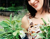 Close Up of a Young Woman Picking Up a Potted Plant at a Garden Centre