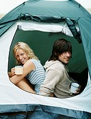 Young Couple Sitting in a Tent Holding Mugs
