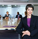 Confident Female CEO Sitting at a Meeting Table, with People in the Background