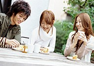 Three Young Friends Around a Wooden Table, Enjoying an Outdoor Lunch of Muffins and Honey