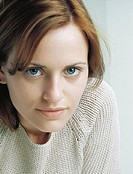 Young woman wearing sweater looking at camera, close-up