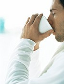 Man drinking from cup, eyes closed