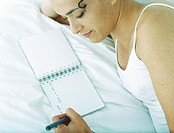 Woman lying on side on bed writing in notebook with pen