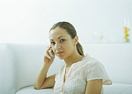 Young woman leaning elbow on sofa, holding cell phone to ear