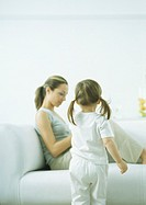 Little girl with pigtails, rear view, and young woman sitting on sofa (thumbnail)