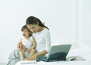 Woman sitting on bed with little girl on lap crying, looking down at paper (thumbnail)