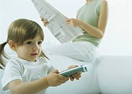 Little girl pointing remote control, woman sitting on back of sofa holding newspaper in background