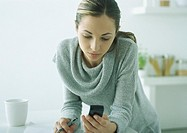 Young woman leaning on table, looking down at cell phone