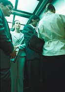 Businesspeople in elevator, low angle view
