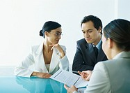 Businessman and businesswoman sitting at table across from businesswoman holding out document and pen