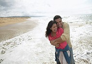 Couple Laughing as They Embrace at the Water´s Edge on a Beach