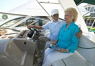 Mature Couple Sitting at the Helm of a Motorboat, Man With his Arm Around the Woman