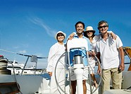 Smiling Family of Four Stand at the Wheel of a Sailing Boat, Mature Son Steering the Boat