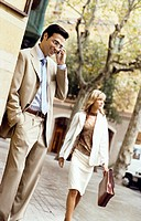 Businessman Using a Mobile Phone and a Businesswoman Walking in the Background