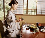 Woman Kneeling and Holding Chopsticks and a Bowl During a Japanese Tea Ceremony