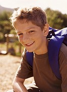 Boy Sitting in the Countryside Wearing a Rucksack