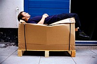 Man resting on cardboard box