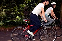Couple cycling in park (thumbnail)