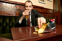 Businessman eating crisps in bar