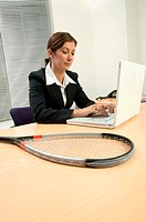 Businesswoman with squash racket on desk