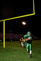 Football player runs with the ball toward Side viewer while opposing player chases after him as he passes the goal post