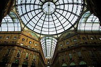 Looking up to the glass domed windows and arches of the Galleria Vittorio Emanuele in Milan, Italy