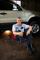 Portrait of a mechanic sitting on a creeper near a car, smiling at the viewer