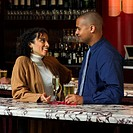 A businessman and woman talk after work in a bar