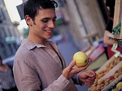 young man taking an apple in grocer´s