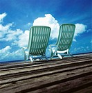 Two reclining white deckchairs looking out towards the sea (thumbnail)
