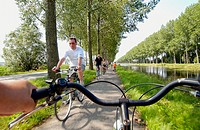 Tourists riding bicycles by canal to Damme, Brugge. Flanders, Belgium