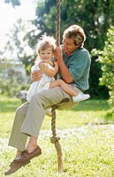 father and daughter on a rope swing