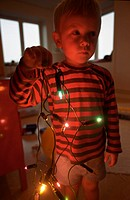 Little boy holding chrismas lights