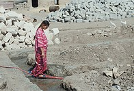 Kurdish woman watering cement for the foundation of her new house Kurdistan Iraq2004